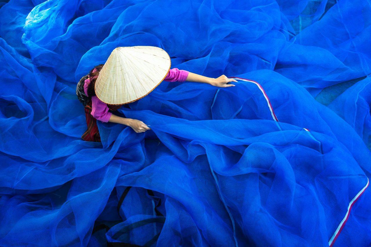 Asian woman organizing blue ocean nets