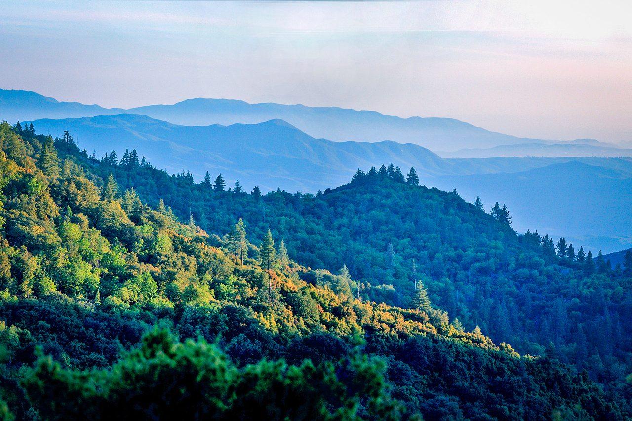 Natural landscape, Sky, Atmosphere, Mountain, Ecoregion, Azure, Cloud, Tree, Highland, Sunlight