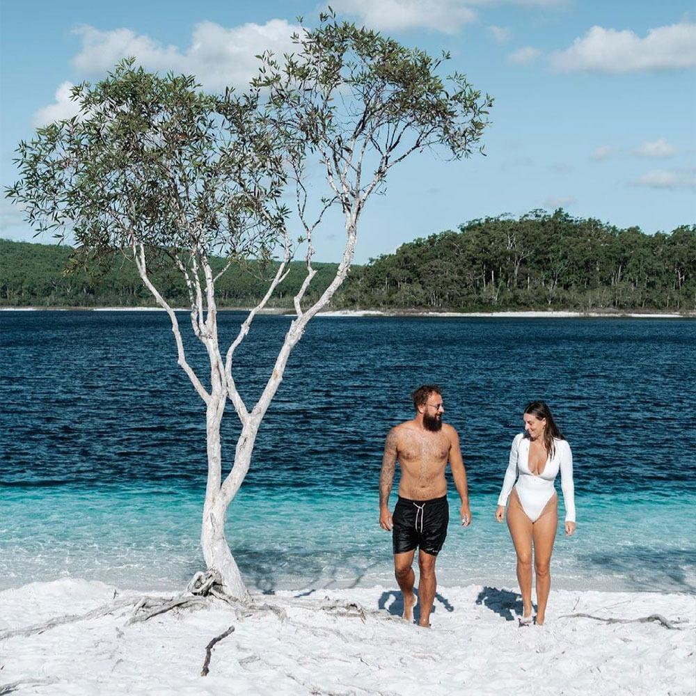 Coastal and oceanic landforms, People on beach, Water, Sky, Cloud, Shorts, Azure, Tree
