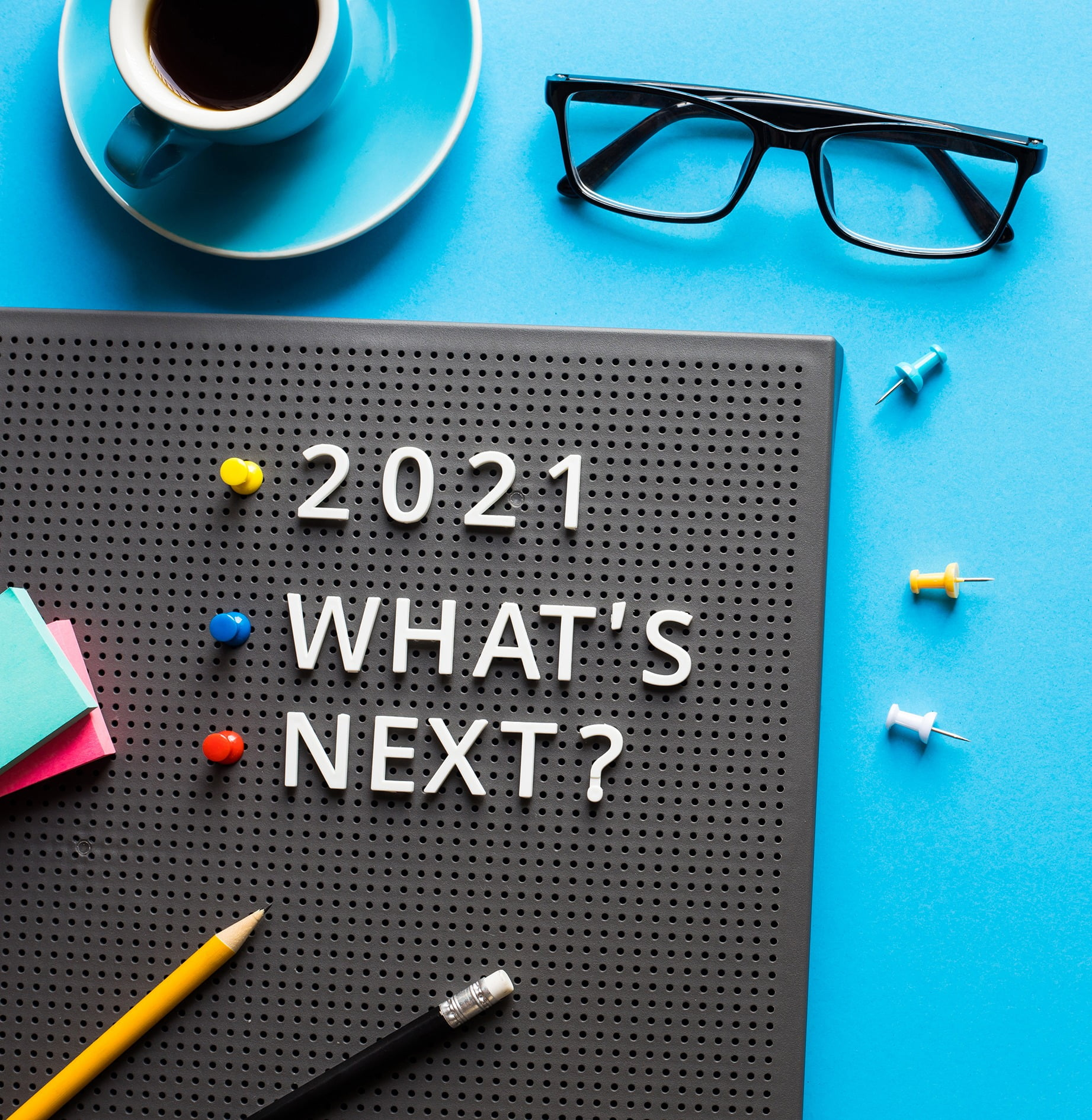 Business corkboard with 2021 Whats Next on desk with coffee, glasses and pencils