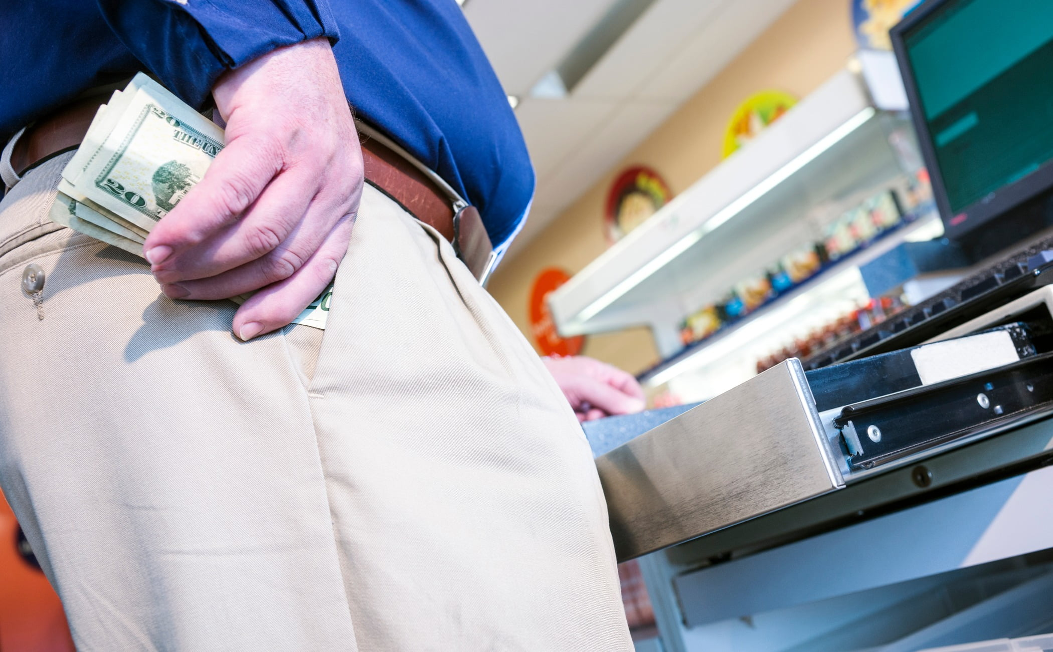 A concept for employee theft and loss prevention. An employee stealing money from a cash register in a retail store.