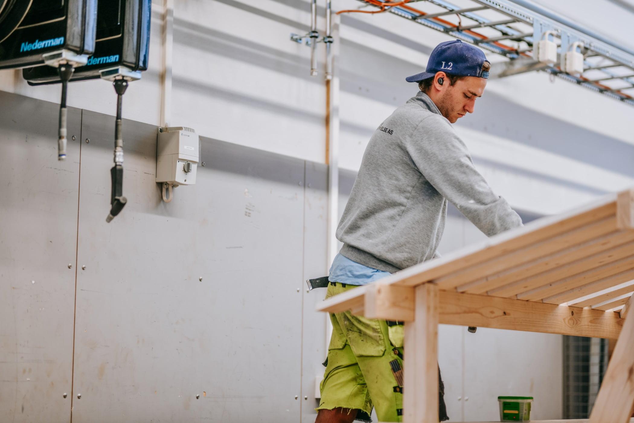 Hard hat, Construction worker, Tradesman, Workwear, Building, Wood, Yellow, Wall, Headgear