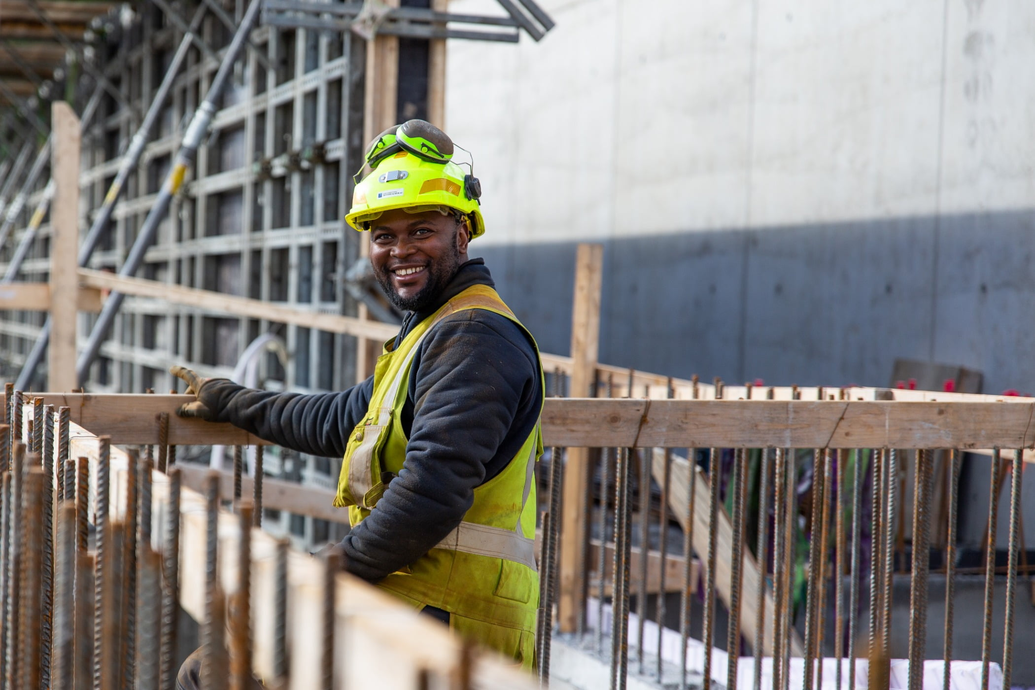 Hard hat, High-visibility clothing, Outerwear, Workwear, Helmet, Tradesman, Engineer, Fence, Smile, Yellow